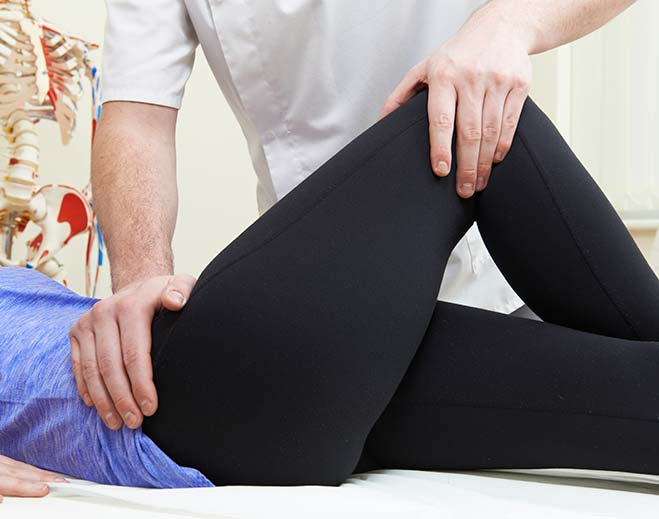 therapist stretching patient's knee